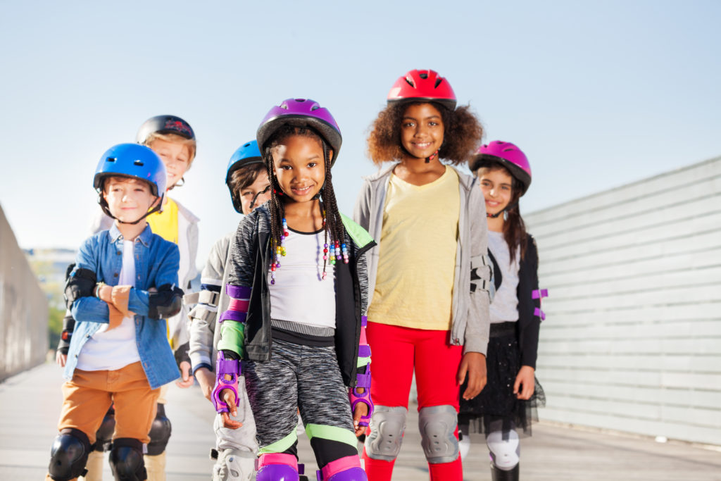 Group of happy sporty kids, preteen boys and girls in safety gear rollerblading outdoors